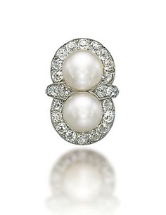 A NATURAL PEARL AND DIAMOND RING  Centering two button-shaped natural pearls, weighing approximately 25.28 and 24.48 grains, to the old-cut diamond surround and shoulders, mounted in platinum
