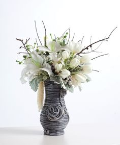 Using woodland elements, unorthodox materials, and sumptuous blooms, Pensacola's Shannon Pallin of Fiore conceives intriguing winter assemblages, such as this white arrangement dressed in a sweater of metallic-silver and gray yarn [Winter 2011, Department: Flower Show, Photography: Cook Images]
