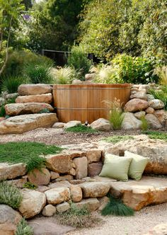 barrel - half sunken with big flat stones, placed high for view,  stone steps to one side, aesthetic placed levels, cushions, grass, rock plants - but grass the gravel please