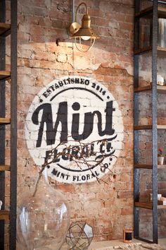 Mint already had such an awesome logo that I wanted to display it somehow on the brick accent wall. I had the idea to have a stencil made and I couldn't be happier with how it turned out. I hung a beautiful, yet simple pendant lamp over top to quite literally shed some light on their logo. I love the overall effect it created and has a graffiti appeal which I adore! Photography by @mangoreclaimed
