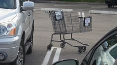 This cart is obviously attempting to impress a few cars by trying to take a parking spot. The cars do not appear to be very impressed. Carts seem to have this ego thing where it's important to fit in with larger wheeled objects. Carts are really quite humble.most of the time.