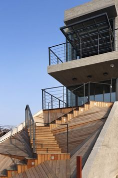 A zig-zagging timber stairway links the first floor of this glass and concrete cultural building  to the ground.