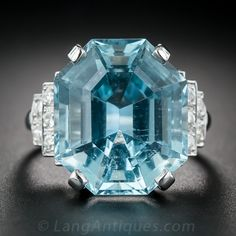 17.42 Carat Aquamarine Art Deco Platinum and Diamond Ring. This cool and refreshing, luscious liquid blue, 17.42 carat aquamarine boasts a striking and distinctive octagonal outline, ideal for this classic Art Deco cocktail ring. The captivating gemstone glistens above and between a pair of sparkling, three-tiered diamond-studded steps crafted in platinum
