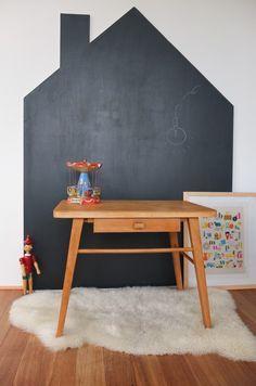 Tafelfarbe im Kinderzimmer: Für die Wandgestaltung mit Tafellack wurde hier einfach ein Umriss in Form eines Hauses gezeichnet und ausgemalt. Perfekt als Kindergrund für einen Kinderschreibtisch. Lediglich beim Schaffell bin ich mir nicht sicher, ob das so gut zu möglichen Kreidekrümeln passt.