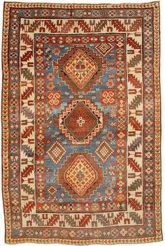 Caucasian Kazak, 4ft 5in x 6ft 9in, Late 19th Century. The best of the naive, geometric Caucasian Kazak antique rugs woven by the nomads who inhabited the highest reaches of the rugged Caucasus Mountains are prized both by serious collectors and lovers of abstract art. This vigorous, extremely elemental Caucasian Kazak rug presents intriguing, archetypal motifs, including three ascending Wheel of Life medallions set upon a seldom-seen, stunningly beautiful cerulean base.