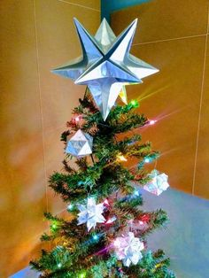 """This listing is for a silver star origami Christmas tree topper hand-folded from premium heavy weight foil wrapping paper.  The paper is embossed with a ribbon pattern and has an elegant silver luster.Regular tree toppers span over 10"""" from tip to tip, suitable for most trees.  7"""" mini stars and 14"""" jumbo stars are also available.Comes securely shipped surrounded by shipping popcorns.  Save the packaging for post Holiday storage.Happy Holidays!!! Origami Tree, Origami Christmas Tree, Christmas Tree Storage, Merry Christmas, Holiday Storage, Silver Christmas Tree, Origami Stars, Christmas Tree Toppers, Xmas Tree"""