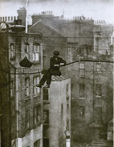 England: London in the telephone engineer, 50 feet up. The engineer is attaching the main telephone cable to a new support wire, suspended between Maddox Street and Conduit Street in Mayfair. Pub Vintage, Photo Vintage, Vintage London, Old London, London City, Mayfair London, 1920 London, Vintage Pictures, Old Pictures