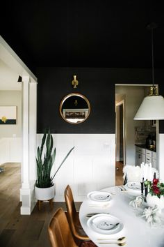 Black dining room with white tulip table. Mixed dining room chairs.