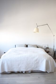 "Sneak Peek: Naomi Ben Shahar. ""We keep the bedroom very spare. It is mostly white but not only white. We love the linens of LA- based Matteo, where the quilt is from. There is a drawing of me by my daughter, and the Tolomeo Mega Floor lamp."" #sneakpeek"