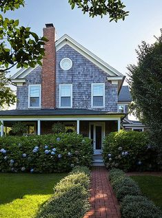 Stunning Hamptons farmhouse home with a shingled exterior, blue hydrangeas and a brick pathway through the front lawn.