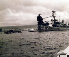 80-G-32610: USS Arizona (BB 39) burning after the Japanese attack on Pearl Harbor, 9 December 1941. Tug is along side.