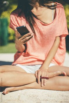 Young woman sitting with her legs crossed and texting with her cell phone.