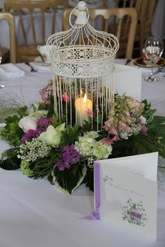 Bird cage centrepiece complete with candle and surrounded by fresh flowers