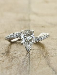 The Celeste is our sculptural take on a traditional engagement ring. It features a unique wave-like band that elegantly contours the finger. Our client requested a brilliant pear shaped diamond sit atop the band in a 5-prong setting. The band is adorned with sparkling white diamonds that creates a brilliant and stunning look.