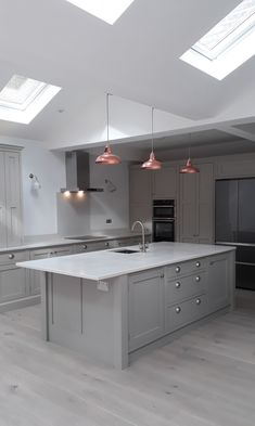 A beautiful example of one of our handmade bespoke kitchens finished in a soft grey with white quartz worktops, undermounted sink and copper light pendants