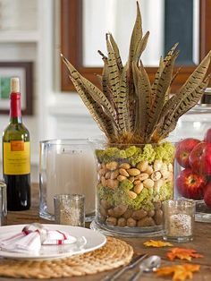 african table decoration ideas | Thankgsiving centerpiece made of nuts, feathers and moss