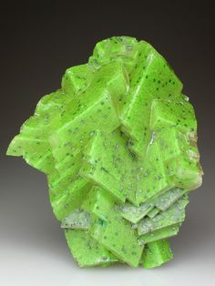 Calcite with Duftite | ©Crystal Classics  Tsumeb Mine, Tsumeb, Otjikoto Region, Namibia.  Mid-green Duftite has been deposited over much of the display face of the Calcite specimen, which in-turn has been covered in a thin veneer of colourless Calcite. Spotted over the Calcite crystals are spherulites of green Malachite.