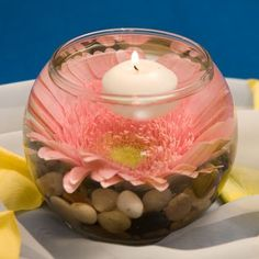 Floating candle with pink Gerbera daisy and river rocks.