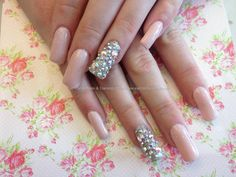Acrylic nails with pink gel polish and Swarovski crystals on ring finger