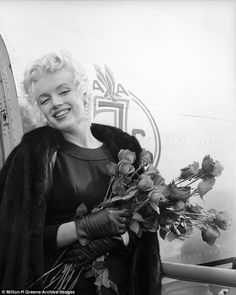 The blonde bombshell smiles while carrying a bunch of roses in Milton H Greene's 'The American Airline Sessions', taken in Los Angeles in 1956