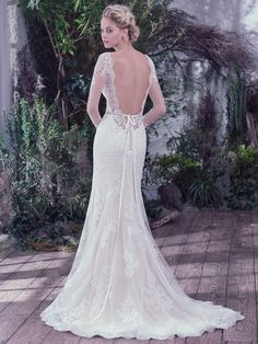 This classic sheath wedding dress features embellished illusion lace over jersey & atop a feminine sweetheart neckline and long sleeves with hand-placed lace appliqués. Complete with a dramatic illusion scooped back and scalloped hemline. Finished with covered buttons over zipper closure. Detachable beaded belt sold separately.