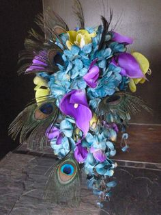 Cascading bridal bouquet with teal hydrangeas, purple calla lilies and orchids, peacock feather accent