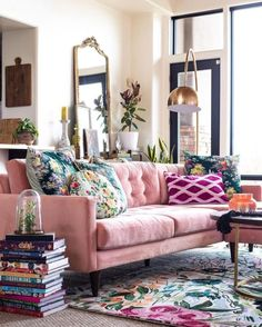 Family room with pink velvet Joybird Elliot sectional. Bari J. for Loloi Rugs Wild Bloom floral rug. Ballard Designs mirror. Stacks of books. House plants. #maximalistdecor #maximalism #boho #frenchbo…