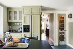 Glass-front uppers and an ornate screen door on the pantry add period detail while allowing the cook to quickly scan shelves.