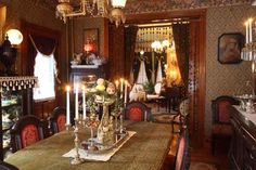 The dining room (in the foreground, with the music room beyond) does not have electric fixtures. The wallpaper is from Thibaut's Historic Home Collection. Note the double portiere; a beaded valance faces the dining room..