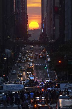 People take pictures of sunset on 42nd street, during the Manhattanhengein New York City