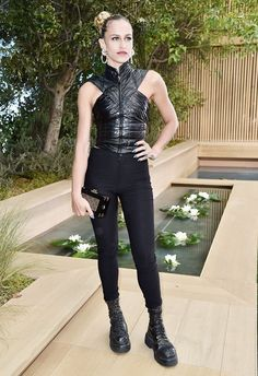 Alice Dellal wears a leather top, skinny jeans, a box clutch, and combat boots