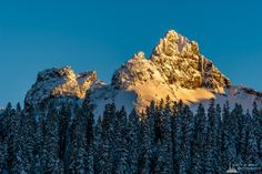 A landscape photograph of the last rays of the winter sunlight (alpenglow) shining on a snow-covered Pinnacle Peak, captured along the Paradise Road at Mount Rainier National Park, Washington.