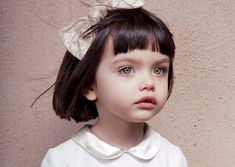 most beautiful little girl with a little bob haircut and bangs.