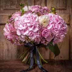 A decadent happy pink with a wash of astrantia, nautica roses and accented with bubble gum scented wax flower.