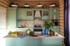 minty green country kitchen cabinets, with a matching kitchen island, vegetables and canned preserves in jars, four hanging lamps, walls covered with wooden planks Rustic Kitchen Island, Rustic Kitchen Cabinets, Kitchen Furniture, Kitchen Dining, Kitchen Decor, Furniture Ideas, Furniture Dolly, Bedroom Furniture, Green Country Kitchen