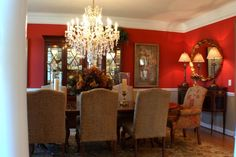 Red walls with white, black and wood tone furniture. White trim really makes the bold red walls pop.