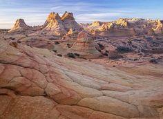 眺望日出時分的 #卡納布市狼丘南區 #Coyote_Buttes_South,陽光落在 砂岩 Sandstone 形成的岩壁, #美國 #US #猶他州 #Utah。砂岩是一種沈積岩,主要由砂粒沈積形成,由於沈積環境的差別,砂岩可能出現不同顏色,包括棕色、黃色、紅色、灰色、白色等。為保護狼丘南區的自然風貌,美國土地管理局規定每天的參觀人數不得超過20人。攝影師:David Clapp