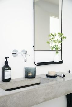 Cement sink in a white bathroom. Love the mirror and the metal tray attached to it. Possibilities of display!!! #MinimalistBathroom