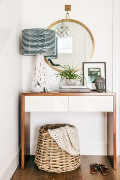 A round mirror, wood lamp and wicker basket. Perfect entryway!