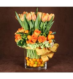 Tulip Hedge Redondo Beach flower delivery 20 stems of gorgeous Dutch tulips are elegantly displayed in this hedge-style arrangement. Accented by lush roses, hydrangea, and coffee bean at the base and completed with wired French ribbon and citrus in the oval vase.