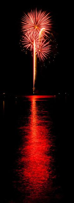 Bursting Of Red 'red fireworks over a lake with a beautiful reflection' - by Chad Cooper .