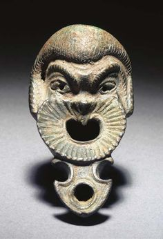 A ROMAN BRONZE LAMP IN THE FORM OF A COMIC SLAVE'S MASK 1ST CENTURY A.D.