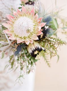 King Protea, Mink Protea, seeded Eucalyptus, Grevillea, Sea holly/ Blue thistles, green Lotus pods, Tillandsia + pink Jasmine, adorned with a gold Chrysina beetle (Floral Design: Passion Roots) - Elegant Oahu Wedding captured by Austin Gros - via ruffled