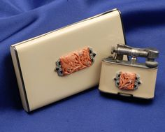 Art Deco Enamel and Gem-set Cigarette Case and Lighter, the sterling silver and ivorytone enamel lighter with platinum, carved coral, onyx, and rose-cut diamond melee mount, French import stamp, signed Alfred Dunhill, Paris, the matching case with gilt interior, no. 4977, maker's mark and guarantee stamps, 1 1/2 x 1 5/8, 3 1/4 x 1 7/8 in. Skinner Auctions 12 june 2007, Sold for:      $1,763.