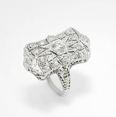 Antique segmented diamond ring in 18k white gold. This feminine, unique ring is set in 18k white gold. The delicate shank flows into a beautiful, star shaped filigree design surrounded by segmented millegrain pieces that each carry their own round brilliant diamond on the surface. Simply an eye-catcher.