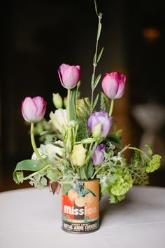 A rustic, arrangement in an antique fruit can,  using, hot pink tulips, cream lisianthus, purple lisianthus, light pink veronica, viburnum and fresh oregano. A wedding reception held at The Calcasieu  in New Orleans.