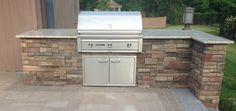 Built-in gas grill with cultured stone veneer, stone countertops, and lighting. Grill Stone, Patio Grill, Outdoor Kitchen Design, Outdoor Kitchens, Long Island Ny, Built In Grill, Grill Design, Summer Kitchen, Stone Countertops