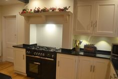 This kitchen features a large island, tall fridge freezer housing, range cooker mantle and black granite worktops. Range Cooker, Cooker Hoods, Tall Fridge, Granite Worktops, Kitchen Cabinets, Kitchen Appliances, Handmade Kitchens, Red Roof, How To Cook Pasta