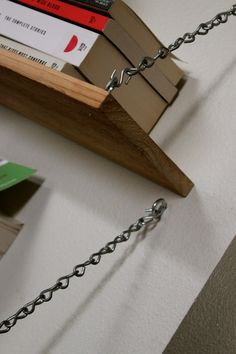 planks hung with L-brackets and chain links - although i would consider paintings the chains.