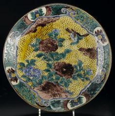 DescriptionDish of heavy porcelain painted in brilliant green, yellow, aubergine and blue glazes with a bird in flight above peonies: Japan, 1868-1912Production informationJapan, East Asia, AsiaMaterialPorcelain